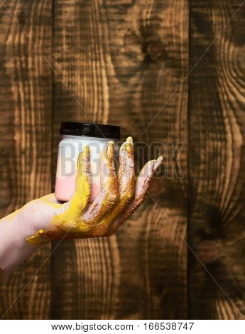 female hand smeared in golden glister holding jar with colorful paint on brown vintage studio background selective focus