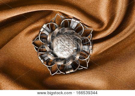 Vintage bronze brooch on orange draped satin closeup