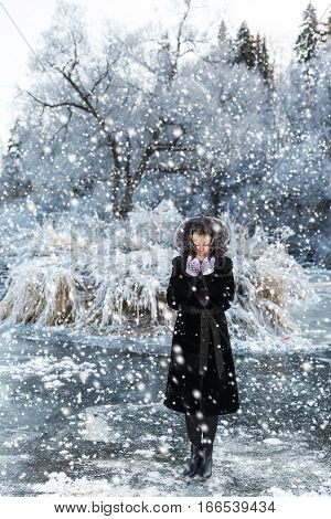 Winter landscape, girl in a black fur coat on a background river under the ice and snow, tree branches covered with white frost