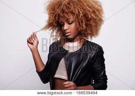 Black Woman Toches Her Curly Blonde Hair Wears Leather Jacket