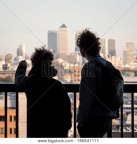 LONDON UK - 2 NOVEMBER 2016: Anonymous tourists looking over the London skyline from the top of the Tate Modern viewing platform with the skyscrapers of Docklands visible in the background.