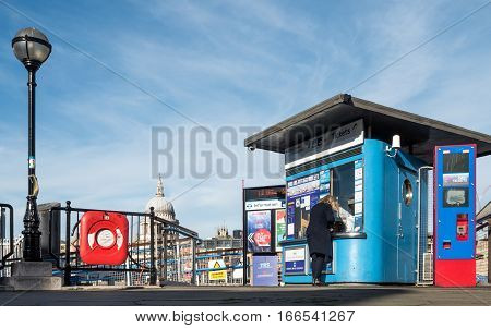 LONDON UK - 2 NOVEMBER 2016: A lady buying a ticket at the Bankside river bus ticket office on the River Thames. The dome of St. Paul's cathedral is visible in the background.