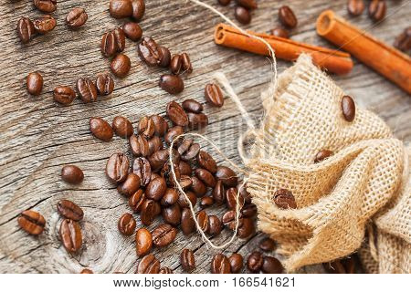 Roasted coffee beans, burlap sac, rustic wooden table, cinnamon. Vintage background . Top view