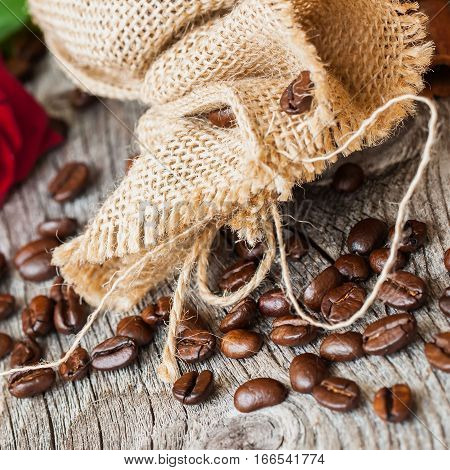 Roasted coffee beans, burlap sac, rustic wooden table, cinnamon. Vintage background . Place for . Top view, grunge texture