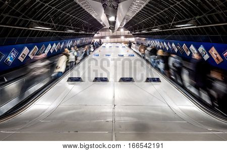 LONDON UK - 2 NOVEMBER 2016: Wide and low angle long exposure blur of tube train travellers and commuters using the escalators at the busy London Bridge underground station.