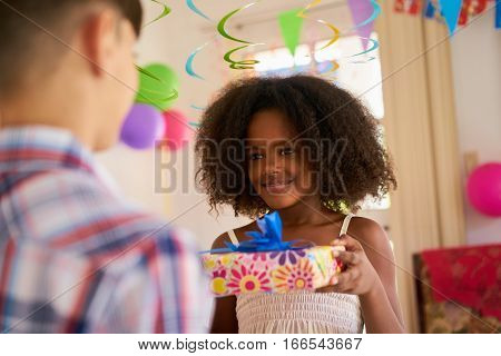 Group of happy children celebrating birthday at home kids having fun at party. Cute black girl giving gift box to friend.