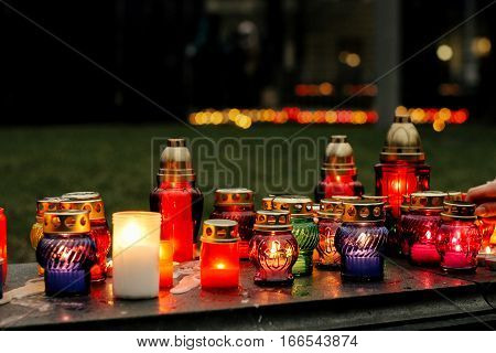 Many Colorful Candles With Light Burning In City Center On Marble Stone, Memorial Day And Sad Bereav