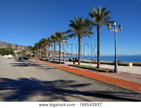 Aguadulce Spain-December 26 2016: People walking along the seafront promenade of Aguadulce. Aguadulce is a spanish locality of Roquetas de Mar province of Almeria. Spain