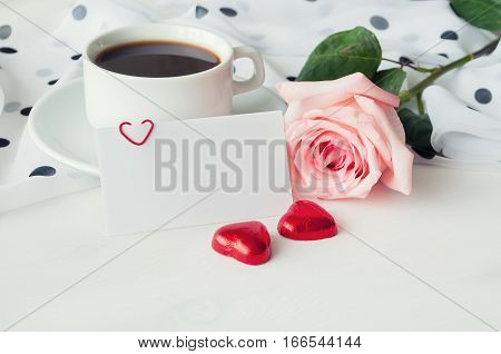 Romantic love background - cup of coffee rose blank love card and two heart shaped candies. Romantic still life with romantic breakfast concept. Romantic card with free space for text