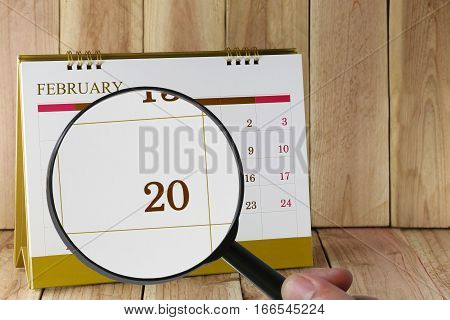 Magnifying glass in hand on calendar you can look Twentieth day of monthFocus number twenty in FebruaryConcept in business and meetings.