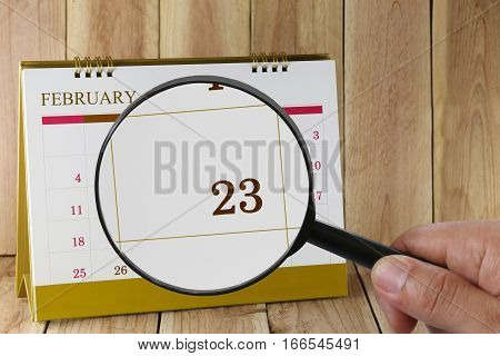Magnifying glass in hand on calendar you can look Twenty-three day of monthFocus number Twenty-three in FebruaryConcept in business and meetings.