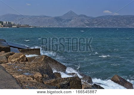 On the rocky embankment Heraklion. View of sea and mountain in the distance the coast