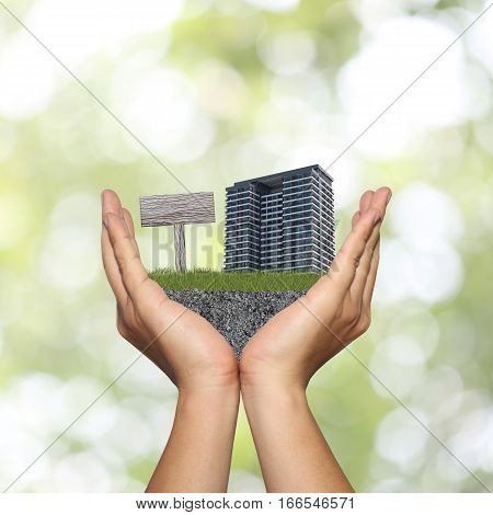 Hand of man and green lawn with condominium and wooden signs in concept of advertising and PR Residential.