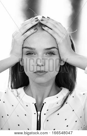 Pretty cute young woman or girl with long blonde hair put her hands on head in blouse with stars outdoor black and white