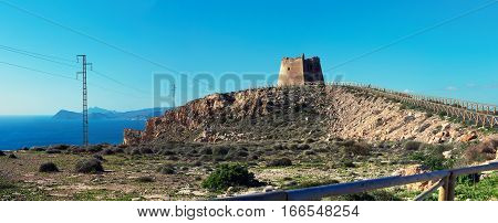 Panoramic view of Mesa Roldan tower of 18th Century lies on a mountain east of the village of Agua Amarga in the province of Almeria. Cabo de Gata-Nijar Natural Park. Spain