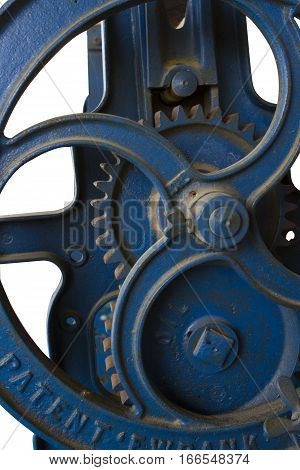 Close up of a portion of blue antique farm equipment showing a wheel and cogs on white