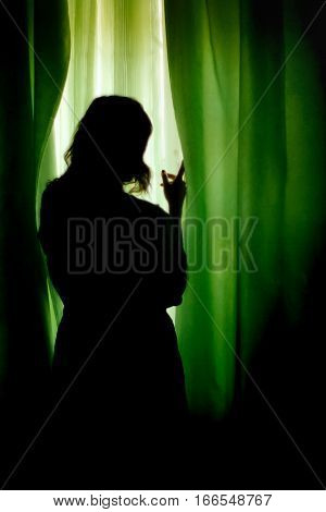 Silhouette Of Beautiful Woman Standing At Green Curtains And Looking At Window