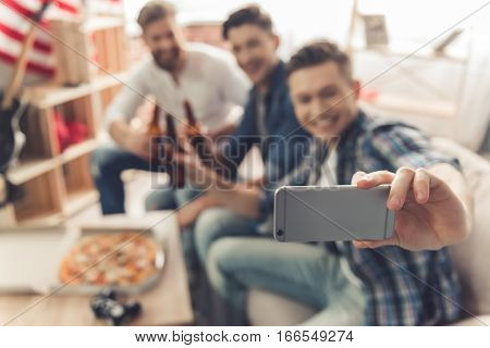 Attractive guys are drinking beer doing selfie using smart phone and smiling while sitting on couch at home