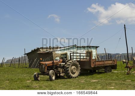 Rural African village house with a tractor in the foreground