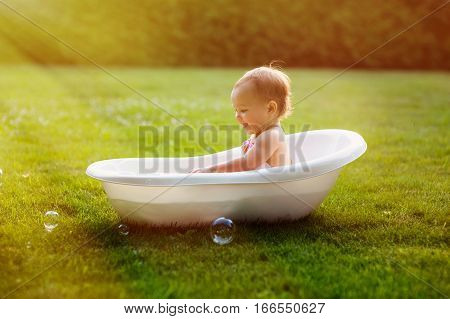 little baby girl bathes in a bath on a meadow.