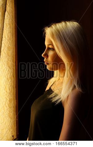 Beautiful young blonde girl. Dramatic portrait of a woman in the dark. Dreamy female look in twilight. Female silhouette in the shadows.
