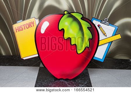 An apple and school supplies decoration sign