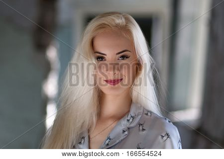 Beautiful young blonde girl with a pretty face and beautiful eyes smiling. Portrait of a woman with long hair and amazing looks. Looking hot girl with a tender look.