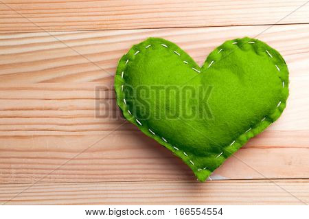 Green heart on natural wooden table on Valentine's Day. Pantone greenery color theme. Copy space on the left.