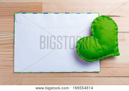 Green homemade heart on a love letter on Valentine's Day. Pantone greneery color theme. Blank envelope. Natural wooden table. Copy space.