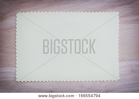 Yellow paper blank on the brown wooden floor of vintage color and You can input the message in copy space.