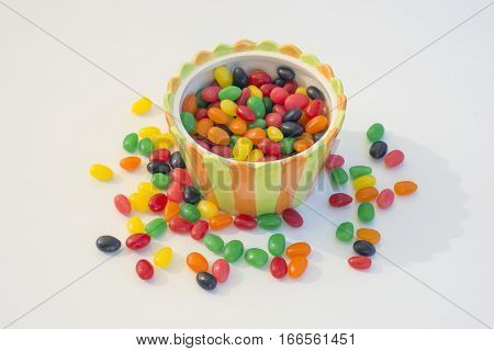 Multicolored jelly beans in a vibrant striped candy bowl