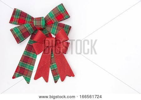 Large red and green plaid bow with smaller red holiday bow on white background