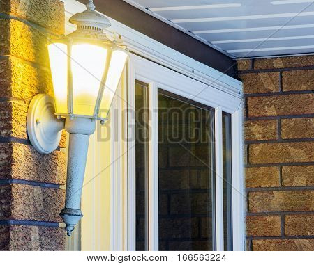 Elegant ornate porch light glowing by front door welcoming inviting scene