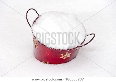 Red Christmas painted bucket sitting in winter snow and filled with powdery snow