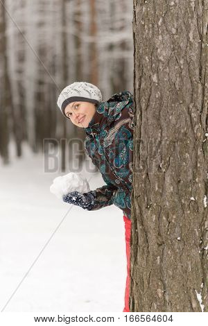Beautiful smiling girl playing in the snow and preparing to ambush behind a tree with snow in hands
