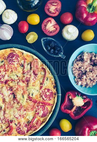 Hot true pepperoni italian pizza with salami and cheese on the table with ingredients. Delicious fresh homemade pizza with salami mushrooms tomatoes pepper. Italian food concept. Top view.