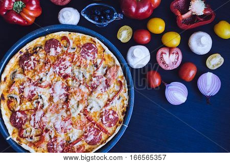 Hot true pepperoni italian pizza on the table with ingredients. Delicious fresh homemade pizza with salami cheese mushrooms tomatoes pepper. Italian food concept. Top view. Copy space.