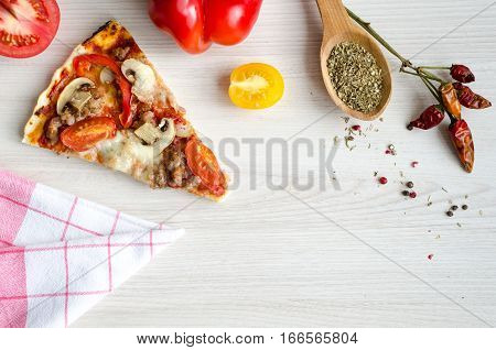 Slice of hot meat italian pizza on white table with spices. Delicious homemade pizza with sausage salsiccia fresca cheese Mozzarella mushrooms tomatoes pepper. Italian food concept. Top view. Copy space.