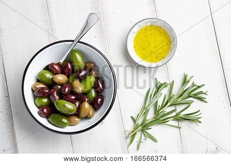 Fresh olives mix, rosemary twigs and olive oil on white wooden background