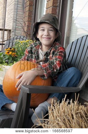 Smiling young boy on country porch hugging a pumpkin in his lap.