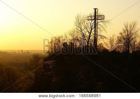 A large cross monument overlooking a misty city landscape at sunset