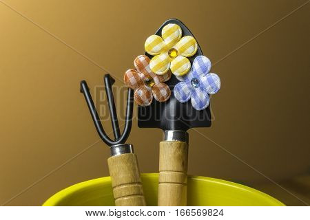 Gardening trowel and fork in a bright yellow planter with plaid country floral decorations