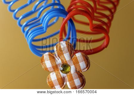 Two heart-shaped slinky toys intertwined with plaid flower decoration love cencept