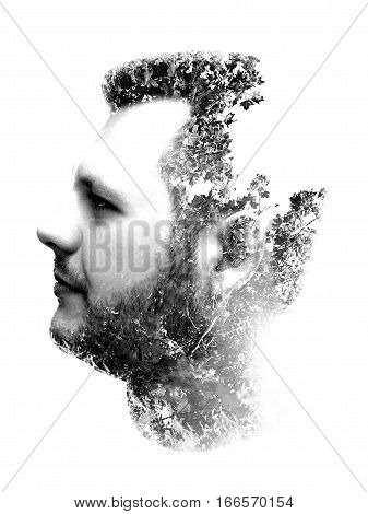 Double exposure portrait of man combined with branches and trees monochrome