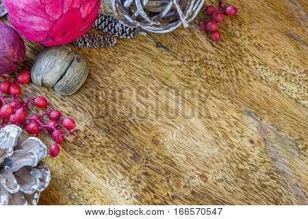 Rustic wooden surface with large potpourri berries and pinecones along top and left border background