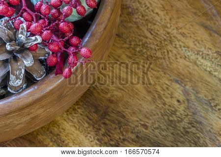 Bowl of pinecones and aromatic potpourri in top left corner of rustic ooden surface background