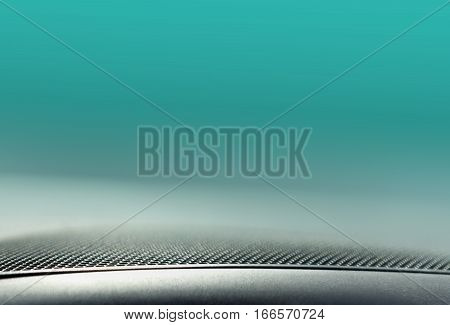 Closeup of speaker sound equipment grate at lower edge of blue light background technology concept