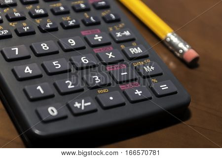 Back pocket scientific calculator and pencil on wooden desk closeup of basic math tools