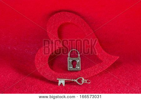 Vintage silver skeleton key and lock in a red heart background love concept