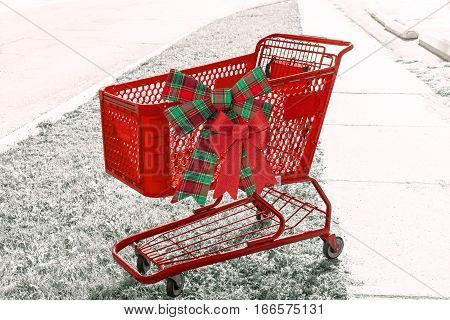 Bright red holiday shopping cart with two bows on desaturated background